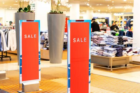 Red bright sale word banner on anti-thieft gate sensor at retail shopping mall entrance. Seasonal discount offer in store.