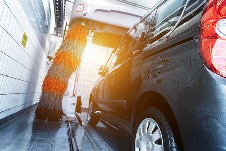 Nettoyage de voiture monospace de livraison moderne noir avec machine de lavage de voiture tunnel automatique robot. Brosses douces grises et rouges lavant le véhicule avec de la mousse à la station de nettoyage de service d'essence à gaz. Entreprise de lavage de voiture. Banque d'images