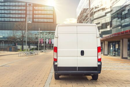 Unrecognizable altered delivery van in european city central . Medium lorry minivan courier vehicle deliver package at residential office building in downtown area. Commercial shipping logistics. Фото со стока