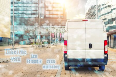 Small cargo electric delivery van driving in european city central district. Zero emission eco-friendly lorry minivan courier vehicle deliver package at office in downtown area. Sustainable logistics. 스톡 콘텐츠