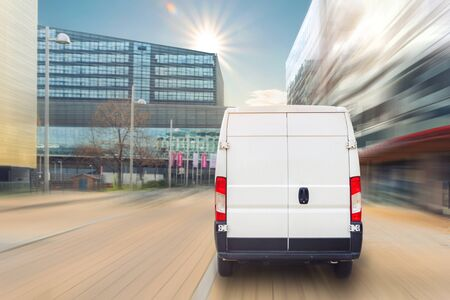 Unrecognizable altered delivery van in european city central . Medium lorry minivan courier vehicle deliver package at residential office building in downtown area. Commercial shipping logistics.