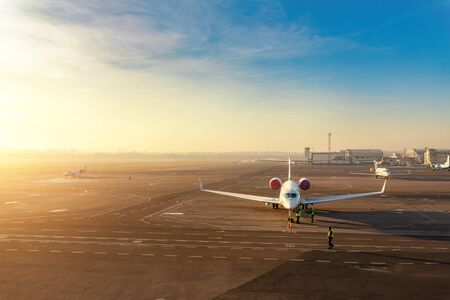 Colorful scenic dramatic morning sunset at airport asphalt taxiway and parking with different commercial passenger airplanes and private jets ready dor departure. Flight tickets booking and charter