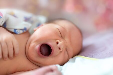 One week newborn adorable innocent baby lying at baycot and funny yawning.Portrait of sleepy caucasian infant tired child on bed. Wide open mouth and closed eyes new born human kid