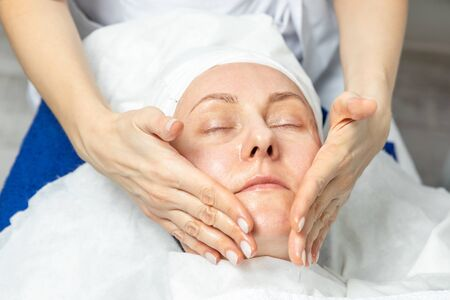 Close-up beautician doctor hands making anti-age procedures, facial and head massage for mid-aged female client at beauty clinic. Cosmetologist doing skincare treatment .Health care therapy