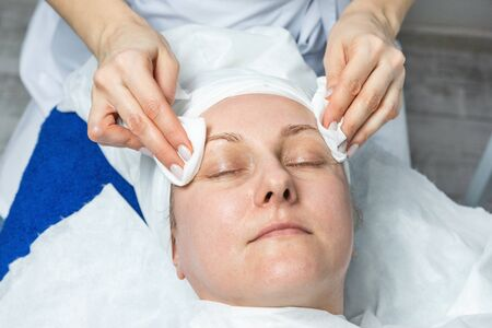 Close-up beautician doctor hands making anti-age procedures, cleaning with napkins facial mask for mid-aged female client at beauty clinic. Cosmetologist doing skincare treatment .Health care therapy 스톡 콘텐츠