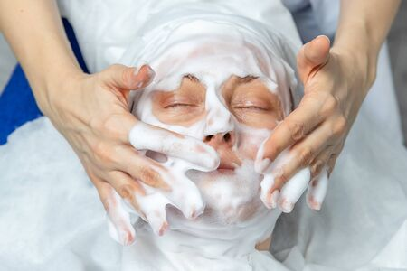 Close-up beautician doctor hands making anti-age procedures, applying foam cleansing mask for mid-aged female client at beauty clinic. Cosmetologist doing skincare treatment .Health care therapy 스톡 콘텐츠