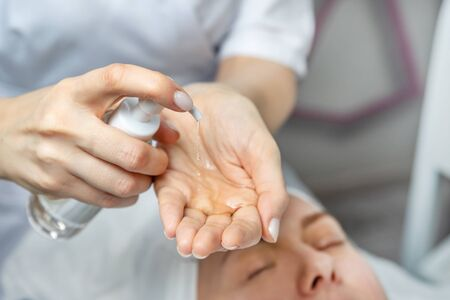 Close-up beautician doctor hands making anti-age procedures, applying cleansing mask lotion for mid-aged female client at beauty clinic. Cosmetologist doing skincare treatment .Health care therapy. 스톡 콘텐츠