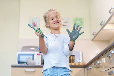 Adorable cute caucasian little blond girl enjoy having fun painting with brush and palm at home indoors on weekend. Cheerful happy child smiling drawing masterpiece art picture. Messy dirty room Banque d'images - 141609195