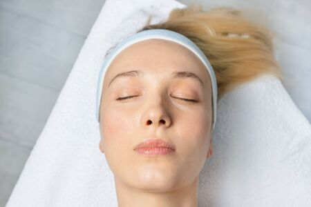 Close-up beautician doctor hand making anti-age procedure, mask and peeling for young attractive female client at beauty clinic. Cosmetologist specialist doing skincare treatment .Health care therapy