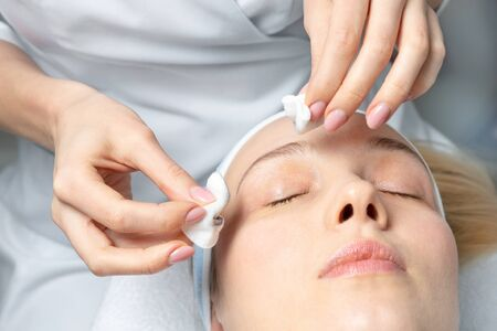 Close-up beautician doctor hand making anti-age procedure, mask and peeling for young attractive female client at beauty clinic. Cosmetologist specialist doing skincare treatment .Health care therapy.