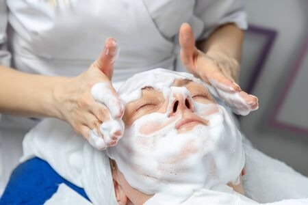 Close-up beautician doctor hands making anti-age procedures, applying foam cleansing mask for mid-aged female client at beauty clinic. Cosmetologist doing skincare treatment .Health care therapy Stock Photo
