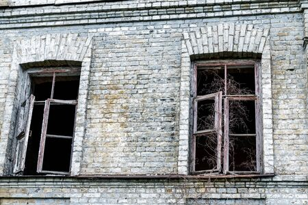 Old shabby ruined abandoned brick building wall facade with two wooden brocken glass windows and dark black background. Shattered grunge aged house exterior. Poverty, decay and breakdown concept
