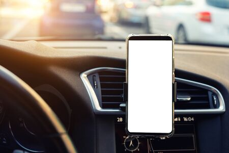 Modern smartphone device gadget mounted on phone holder at car dashboard. Mock-up white screen isolated template. Copyspace for text . Vehicle interior cockpit view. Traffi jam info app.