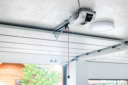 Opening door and automatic garage door opener electric engine gear mounted on ceiling with emergency cord. Double place empty garage interior with rolling entrance gate.
