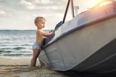 Cute adorable caucasian blond little toddler boy in white pants standing on sandy beach near fishing boat look and dreaming about sailor profession in future. Travel and adventure concept.Summer day. Archivio Fotografico