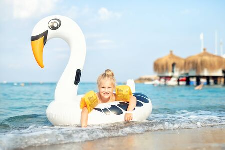 Portrait cute adorable caucasian preschooler blond girl enjoy relaxing with inflatable toy at beach of ocean or sea resort. Cheerful happy child swimming in clean blue water during holiday vacation