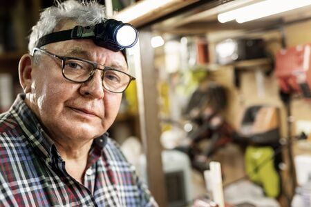 Senior craftsman portrait with headlamp led torch sitting in workhop with tools and equipment on background. Old mature gray handyman tutor with eyeglasses. Experienced person making diy hobby craft