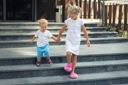 Two cute adorable caucasian blond little siblings walking down stiars residential building. Reliable elder sister support, learnd and help younger toddler brother. Family love, care support Stock Photo