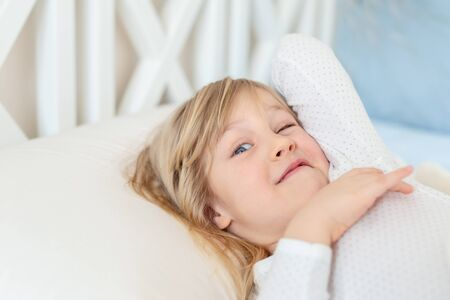 Cute adorable caucasian blond little toddler kid girl lying in bed on white pillow. Adorable sweet happy smiling child wink at wake up early morning for kindergarten or school. Childhood concept. Foto de archivo