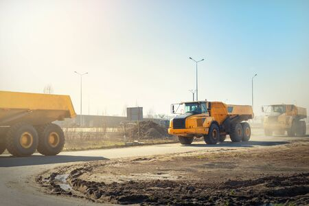 Many big articulated heavy industrial yellow dumper trucks driving on new highway road construction site on sunny day with blue sky background. Construction equipment machinery working on open pit.