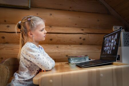 Cute adorable caucasian little blond girl sitting at desk with laptop during online video chat school lesson session with teacher and class. Remote education concept. Self-isolation at quarantine