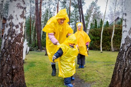 Mother with cute adorable caucasian siblings children in bright yellow raincoat and wellies playing at garden during cold spring rainy day at home backyard. Carefree childhood concept. Bad weather