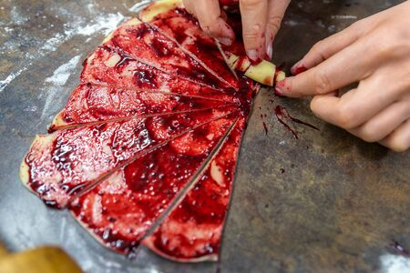 Grandmother making handmade tasty butter rolling cookies with fruit and berry jam on oven tray before baking at kitchen indoor. Rolled spin homemade healthy pastry preparing.