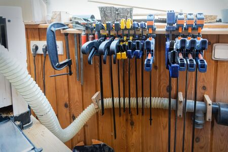 Set of woodworking tools and equipment hanged on wall at carpentry. Different chisels, drills and pencils at craftsman workshop. DIY instruments on wood workbench. Workplace organization arrangement.