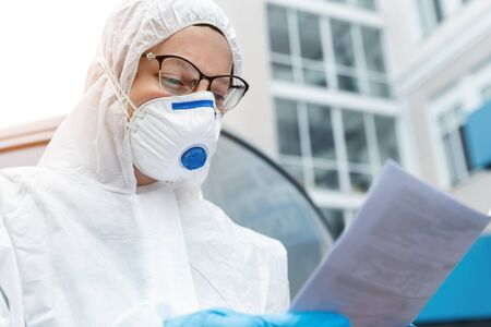 Portrait of tired exhausted female doctor, scientist or nurse wearing face mask and biological hazmat ppe suit reading who treatment protocol or research outdoor. Coronavirus covid-19 outbreak danger