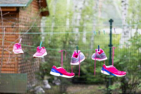 Three pairs of bright sport fitness sneakers hanged on clothespin at backyard after laundry outdoors. Preparartion for running training or marathon