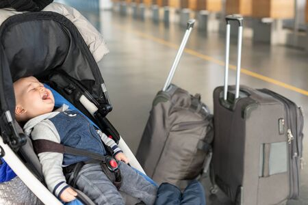 Screaming baby boy sitting in stroller near luggage at airport terminal. Child in carriage near check-in desk counter. Children tears , panic and hysterics. Travelling with small children concept