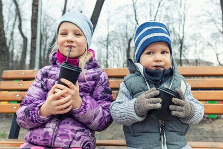 Two cute adorable siblings children sitting on wooden bench and drinking hot chocolate, tea or cocoa from paper cups during walk at city street park or backyard outdoors. Brother and sister enjoy fun