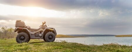 ATV awd quadbike motorcycle pov view near lake or river pond coast with beautiful nature landscape and cloudscape sky background. Offroad adventure trip . Extreme sport activity panoranic wide view. Reklamní fotografie