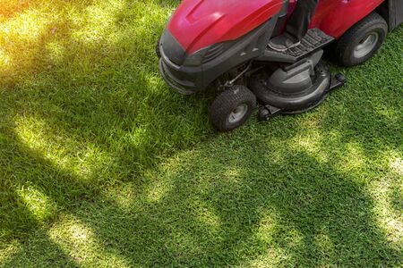 Top down above view of professional lawn mower worker cutting fresh green grass with landcaping tractor equipment machine. Garden and backyard landscape lawnmower service and maintenance.