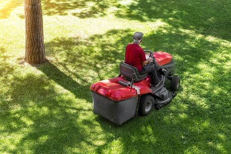 Top down above view of professional lawn mower worker cutting fresh green grass with landcaping tractor equipment machine at city park. Garden and backyard landscape lawnmower service and maintenance.