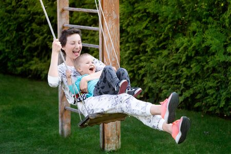 Young adult beautiful caucasian woman enjoy having fun sit and ride rope swing with cute little toddler son at home yard playground outdoors. Happy mom and funny child laughing playing in garden