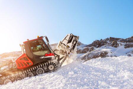 Red modern snowcat ratrack with snowplow snow grooming machine preparing ski slope piste hill at alpine skiing winter resort Ischgl in Austria. Heavy machinery mountain equipment track vehicle.