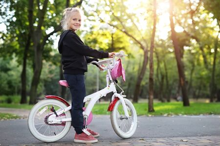 Cute adorable beautiful caucasian little blond girl enjoy riding white small bicycle by path in green summer city park forest or garden at bright sunny day outdoor. Children healthy lifestyle concept