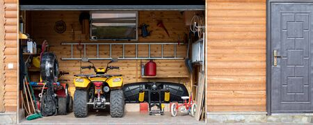 Facade front view open door ATV quad bike motorcycle parking messy garage building with wooden siding at home driveway backyard and lawn path. House warehouse for tools and equipment . Wide panoramic Zdjęcie Seryjne