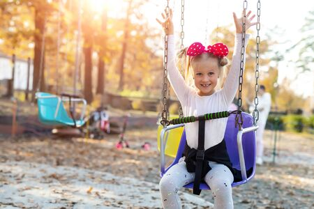 Little cute adorable caucasian blond school girl enjoy having fun sitting and riding old chain swing carousel at city theme amusement park. Happy child portrait outdoors at sunset evening sun light