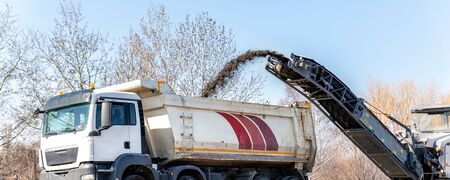 Asphalt milling and grinding machine at road repair and construction site throwing shredded old bitumen in big industrial heavy dumper tipper truck for recycling. Highway renewal with heavy machinery