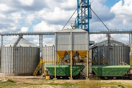 Modern steel agricultural grain granary silos cereal storage warehouse loading railway cargo carriage at sunny day. Agribuisness farmland rural industry landscape scene. Mill store facility. 版權商用圖片
