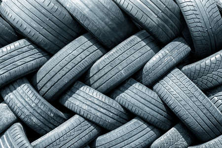 Old used weared car and truck wheels tyres pile stacked in rows stored for recycling. Heap of many rubber tires wall background. Idustrial pollution of environment Reklamní fotografie - 150638004