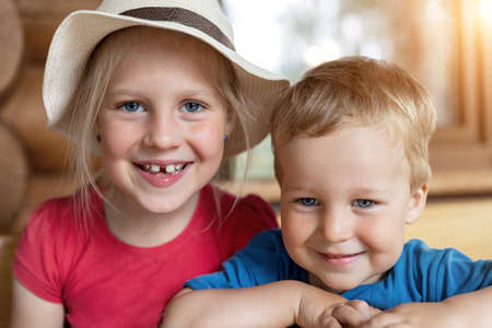 Two cute adorable caucasian blond little siblings sitting at table home yard and having fun play together outdoors. Young happy sister and toddler brother enjoy laughing outside. Family love care 版權商用圖片