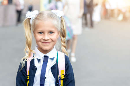Portrait of cute adorable little caucasian school girl with funny blond pig-tails hair wearing uniform and backpack enjoy going back to school. First class primary elementary education happy pupil.