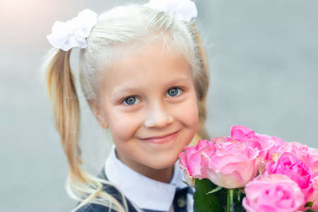 Portrait of cute adorable little caucasian school girl with funny blond pig-tails hair wearing uniform and flowers bouquet going back to school. First class primary elementary education happy pupil.