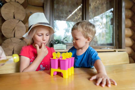 Two cute adorable caucasian blond little sibling sitting at table home yard and have fun tasting mom homemade fruit icecream. Young happy sister and brother enjoy laughing outside. Family love care .