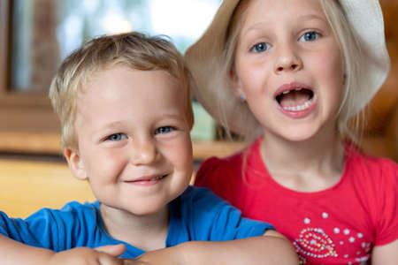 Two cute adorable caucasian blond little siblings sitting at table home yard and having fun play together outdoors. Young happy sister and toddler brother enjoy laughing outside. Family love care .