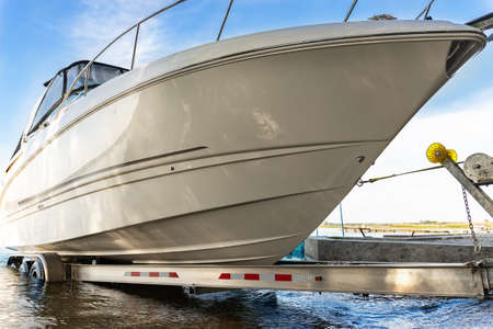 Big luxury cabin motorboat cruiser yacht launching at trailer ramp on river or lake. Warm morning sunrise sunshine reflection in calm water surface. Luxury rich fishing leisure recreation lifestyle
