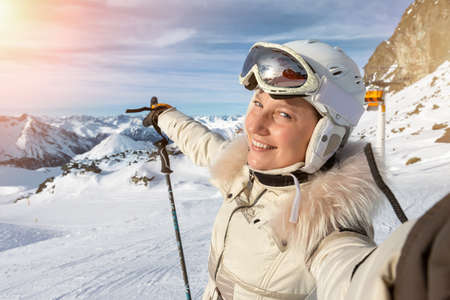 Young adult beautiful happy attractive caucasian smiling skier woman portrait making selfie on mountain peak showing skiing resort panorama breathtaking view. Winter travel adventure welcome concept